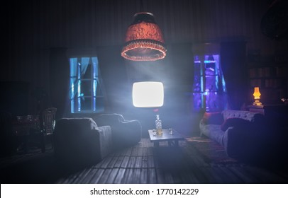 A realistic dollhouse living room with furniture and window at night. Artwork table decoration with handmade realistic dollhouse. Old retro style Television. Selective focus.