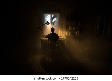 A realistic dollhouse living room with furniture and window at night. Man sitting on table in dark room. Concept of stay home during global virus pandemic. Selective focus.