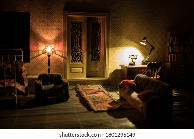 A realistic dollhouse living room with furniture and window at night. Artwork table decoration with handmade realistic dollhouse. Man wathing retro style Television in dark room. Selective focus.