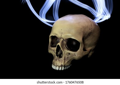 A realistic human prop skull with a missing lower jawbone photographed on a dark background. There are some blue swirling lights behind the skull.
