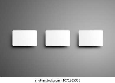 Realistic white mockup of a three  bank (gift) card with shadows placed horizontally on a gray background. Ready to used in your showcase.