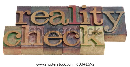 reality check concept  - words in  vintage wooden letterpress printing blocks, stained by color inks, isolated on white