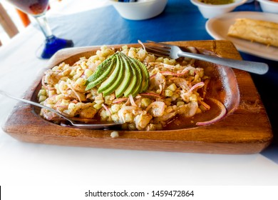 Really good elaborated wooden dish of a typical seafood named aguachile of shrimp and avocado toping