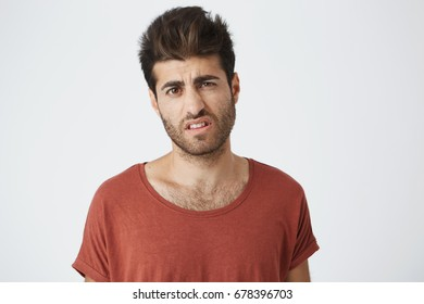 Really Indignant stylish boy with trendy haircut dressed in casual clothing standing at white studio wall, expressing misunderstandment, dislike or disregard, feeling unwillingness towards something.