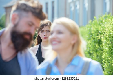Really jealous of him. Jealous woman look at couple in love on street. Romantic couple of man and woman dating. Bearded man cheating his girlfriend with another woman. Unhappy girl feeling jealous.