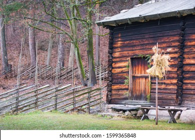 really old Norwegian house with skigard and a sheaf of oats as a bird feederfor the birds outside