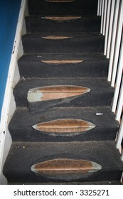 Really tatty carpet on a dark staircase, with holes and wear. In need of recarpeting. Trip hazard