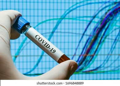 Real-time PCR testing on COVID-19. A test tube with a sample on the background of amplification curves.