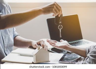 Realtor agent giving keys to tenant after sign agreement to rent property.