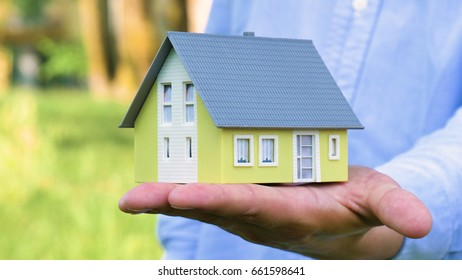 Realtor, broker, businessman is holding a small yellow house for sale, buying or renting real estate, a hand, a blue shirt on a nature background. Concept purchase of a new house, sale of real estate