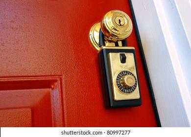 Realtor combination lock box safety key holder on doorknob of a house for sale entrance door for a real estate resale transaction