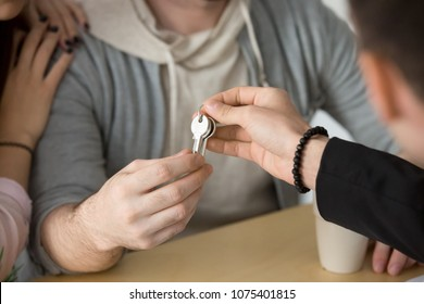 Realtor giving couple keys to own home, family customers buying new house or rent apartment concept, making real estate deal or property ownership, mortgage loan investment, close up view of hands
