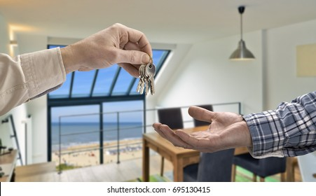 Realtor giving house key to buyer in Modern living room
