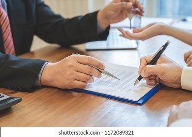 Realtor giving keys to a couple after successful deal, A couple signing contract agreement document, Home loan,buy new home,moving home or renting property concept