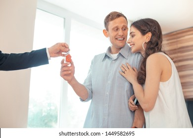 Realtor giving keys. Realtor giving the keys to happy excited couple after buying the house