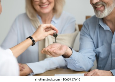 Realtor giving senior aged couple key to new house at meeting, happy older real estate owners make purchase deal concept, smiling elderly family bought or rented apartment, close up view of hands