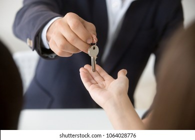 Realtor giving woman keys to new apartment, agent making deal with client buyer owner tenant renter buying or renting real estate, mortgage loan investment and property purchase, hands close up view