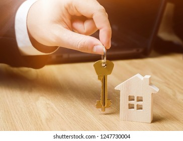 Realtor holds house keys. Real estate agent. Buying and selling a house, apartment. Home rent. Affordable housing. Investment in construction. Planning a new project. Property valuation