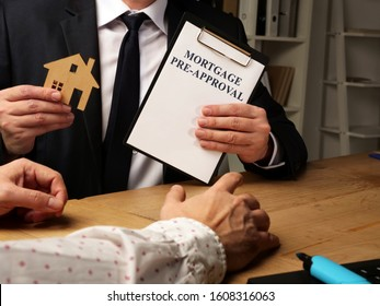 Realtor holds Mortgage Pre-Approval agreement form and model of house.