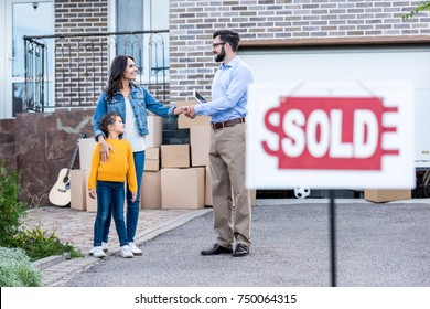 realtor making deal with single mother with sold signboard blurred on foreground