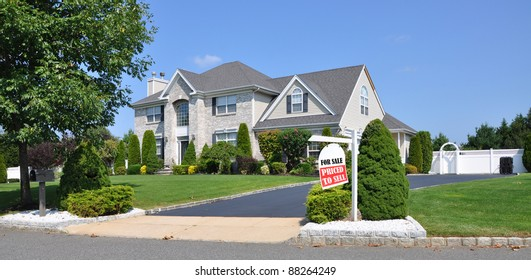 Realtor For Sale Sign on front yard of beautiful landscaped large brick suburban home on sunny clear blue sky day