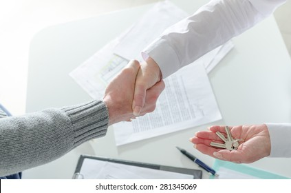 Realtor shaking hands with his client after handing over the keys