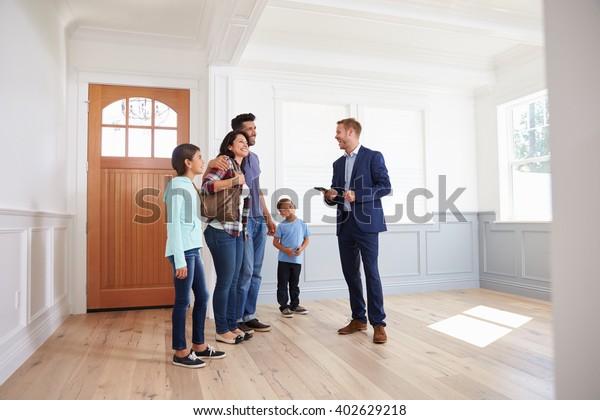 Realtor zeigt hispanische Familie rund um New Home
