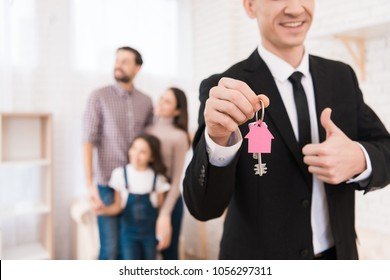 Realtor in suit holds keys with key fob in form of house. Young family looks apartment. Buying real estate concept.