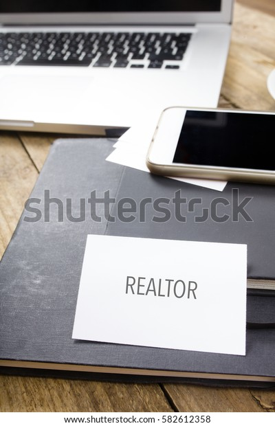 Realtor text on business card at desktop in office with laptop, tablet computer and phone.