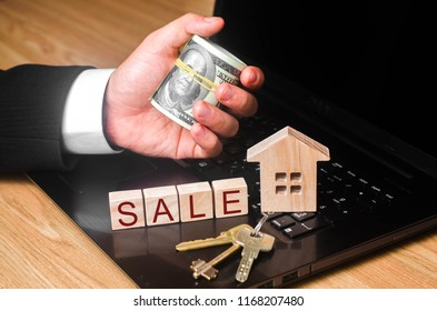 The realtor's hand holds a bundle of money at the house with the keys. The concept of buying and selling real estate, investment. Estimate the value of the house. Loans and mortgages to buy.