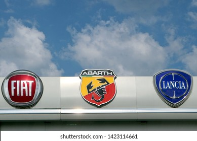 Reana, Italy. June 13 2019. Fiat, Abarth and Lancia logos in the dealership of the area, against a blue sky  with clouds. They are all part of the Fiat Group, italian car manufacturer