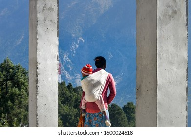 Reang Tribal indian woman mother carrying baby on back Wrap his kid in a piggy back( a traditional child carrier) It is a famous cultural kids wearing used all the World. Mizoram India, South Asia Pac