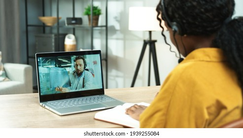 Rear of African American female patient sitting at table in room at home speaking online on video call on laptop with Caucasian man doctor having medical consultation on internet, medicine, close up