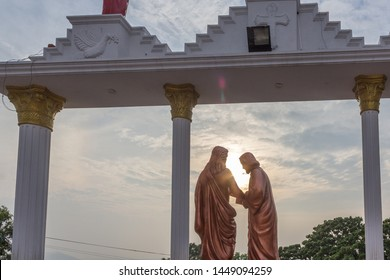 Rear angle view of Jesus healing a man with his power in gold colored stone statue and sunset scene in the background with beautiful colors in the sky