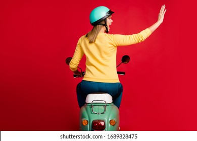 Rear back behind view of her she nice attractive cheerful girl driving moped waving hi new purchase buying transport vehicle owner ownership isolated on bright vivid shine vibrant red color background