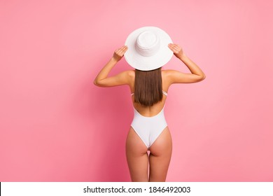Rear back behind view of her she nice attractive well-groomed lovely sporty slim fit thin straight-haired lady perfect shape form figure fixing panama isolated on pink pastel background