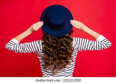 Rear back behind view of nice well-groomed gorgeous attractive wavy-haired lady wearing striped pullover sunhat isolated over bright vivid shine red background