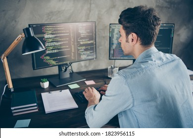 Rear back behind view portrait of his he nice attractive focused geek guy typing css analyzing cyberspace security building at modern industrial interior style concrete wall work place station