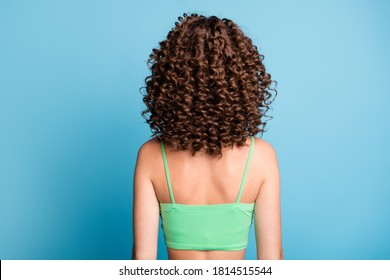Rear back photo of young lady stand big extensive volume hairstyle nice curls sporty athletic trained spine back after exercises wear green crop top isolated blue color background