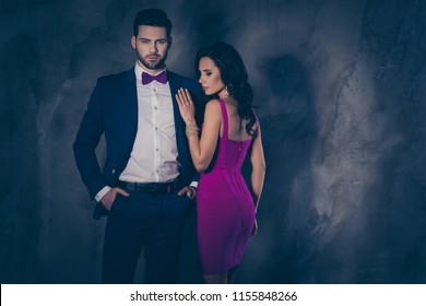 Rear back side view portrait of pretty charming woman with booty butt in lilac dress standing near virile man in tux holding two hands in pockets isolated on grey background with copysapce