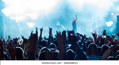 Rear back view of audience crowd people fans raising hands enjoying live music festival concert event concept shooting on phones rock band silhouettes performance sing on night club outdoor stage.