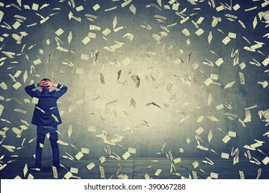 Rear back view of business man standing in front of a wall under money rain dollar banknotes falling down, hands on head wondering what to do next. Full body length of businessman facing the wall