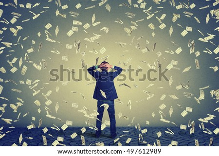 Rear back view of business man standing in front of a wall under money rain dollar banknotes falling down, hands on head wondering. Full body length of businessman facing the wall
