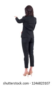 Rear back view of business woman in suit interacting with touch screen or pointing finger at presentation. Full body isolated on white background.