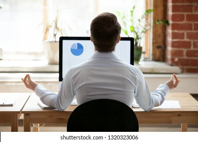 Rear back view businessman sitting at desk opposite pc doing yoga feels placidity and calmness. Employee take break resting relaxing practicing meditation. Healthy lifestyle and stress relief concept