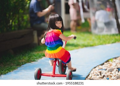 Rear back view of cute Asian girl riding a red tricycle on a small blue road in a playground. Child enjoy exercising. Happy kid wearing a colorful dress aged 4 year old. Children looked back at camera