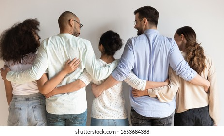 Rear back view of multi-ethnic millennial girls and guys best friends embracing standing near grey wall indoors showing unity and support, concept of friendship, racial equality, teamwork togetherness