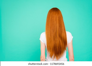 Rear back view of nice attractive bright vivid shiny red straight-haired girl in casual t-shirt, isolated over turquoise green teal pastel background