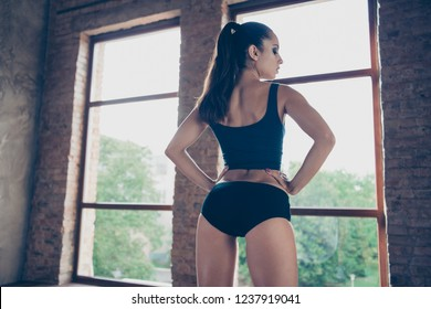 Rear back view of stylish nice beautiful strong model sporty slim lady trainer instructor with pigtail holding hands on waist looking aside at pilates power yoga class