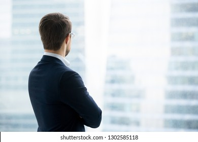 Rear back view of successful rich businessman in suit standing looking through window at modern city buildings skyscrapers thinking of future business vision, dreaming of new opportunities concept